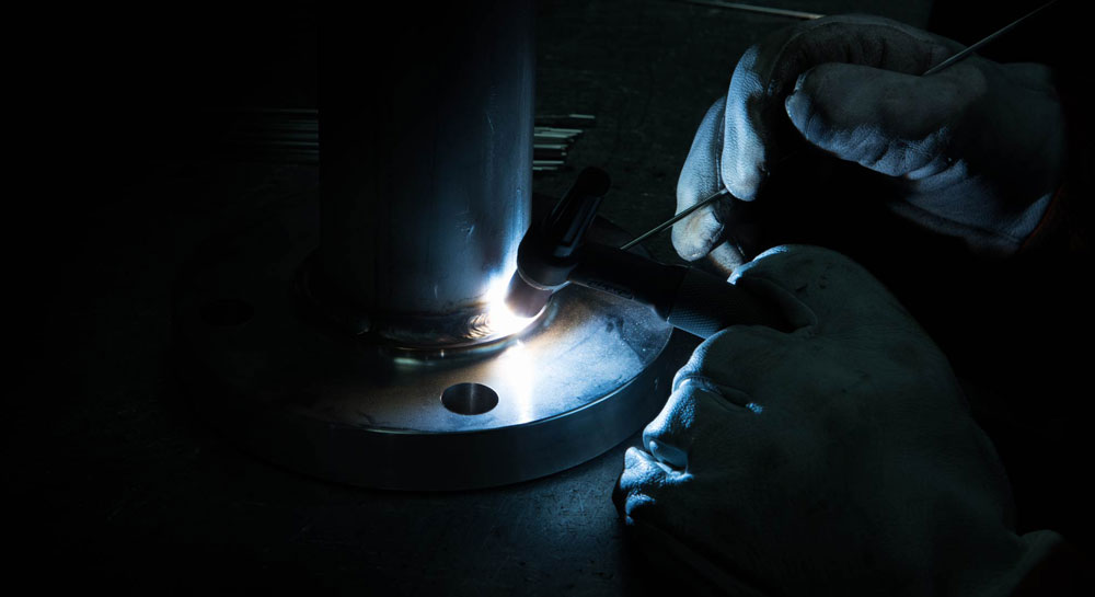 Welder carefully fillet welding a raised face flange to a stainless steel static mixer.
